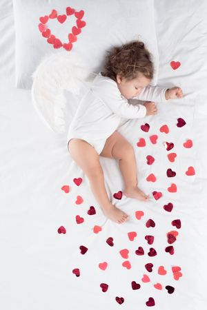 little toddler with wings sleeping on bed with red hearts Banco de Imagens
