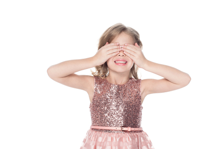 smiling kid in pink dress closing eyes, isolated on white