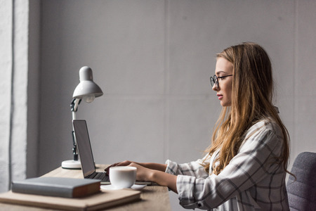 side view of focused young businesswoman working with laptop