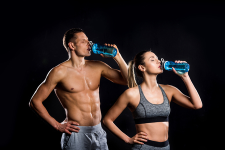 athletic young couple in sportswear drinking from bottles isolated on black