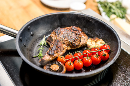 meat with vegetables on frying pan on electric stove