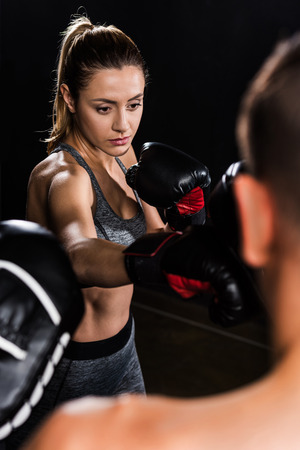 selective focus of young sportswoman boxing with shirtless sportsman