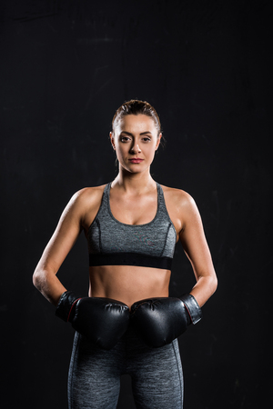 athletic sportswoman in boxing gloves looking at camera isolated on black