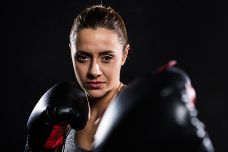 selective focus of young sportswoman boxing and looking at camera isolated on black