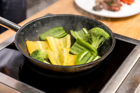 yellow and green bell peppers with broccoli on frying pan