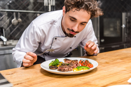 handsome chef standing with fork above fried vegetables with meat