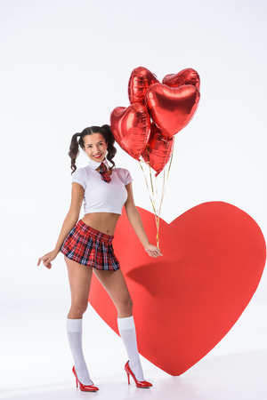 young sexy schoolgirl with helium balloons in shape of hearts in front of big red heart on white