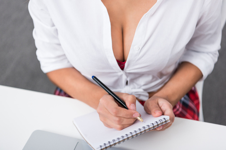 cropped shot of woman in unbuttoned shirt writing in notebook 版權商用圖片
