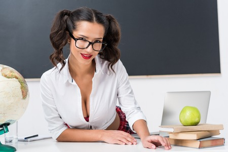 young sexy teacher sitting at workdesk in front of blackboard Standard-Bild