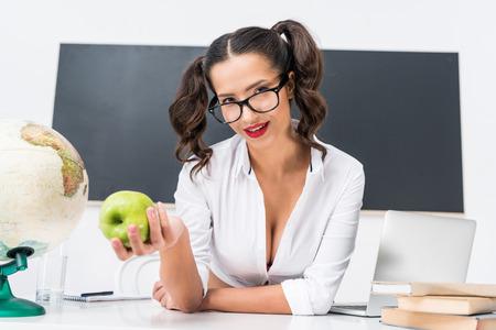 junger Lehrer mit grünem Apfel, der am Arbeitsplatz in der Klasse sitzt Standard-Bild
