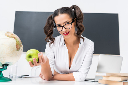 young teacher with green apple sitting at workplace in class