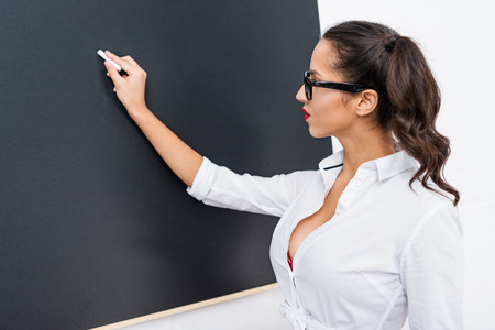 young sexy teacher writing on blackboard with chalk 版權商用圖片