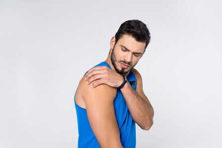 Hombre joven con dolor en el hombro aislado en blanco