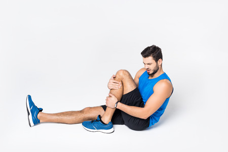 athletic young man with pain in leg sittion on white