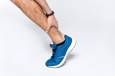 cropped shot of runner holding leg while in hurts on white