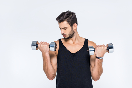 handsome young man working out with dumbbells isolated on white