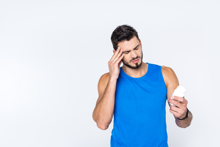 young man with headache looking at jar of pills isolated on white