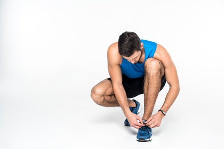 athletic young man lacing up sneakers before run on white