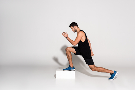 side view of athletic man doing step aerobics on block Stock Photo