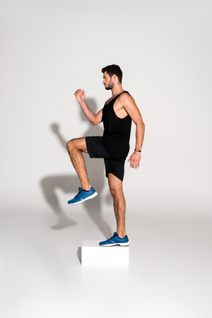 side view of sportive man doing step aerobics on block