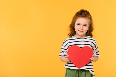 portrait of smiling kid with red paper heart isolated on yellow, st valentines day concept