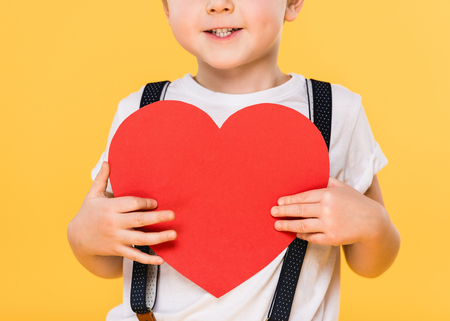partial view of kid with red paper heart isolated on yellow, st valentines day concept