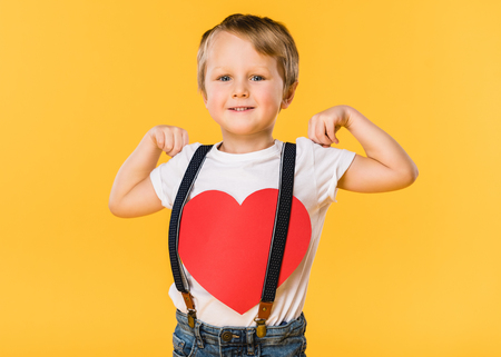 portrait of adorable little boy with red paper heart isolated on yellow, st valentines day concept