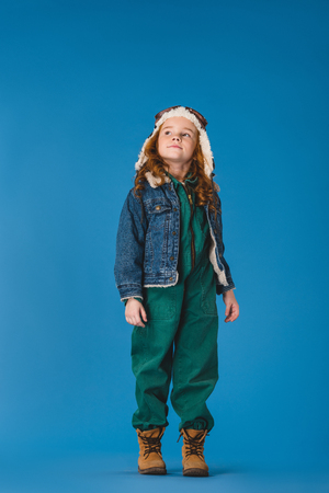 adorable preteen kid in pilot costume looking away isolated on blue Imagens