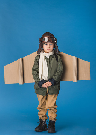 cute little boy in pilot costume with paper plane wing isolated on blue Фото со стока