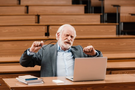 grey hair professor stretching in empty lecture room