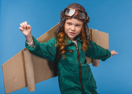 portrait of cute child in pilot costume with handmade paper plane wings isolated on blue Фото со стока - 114471978