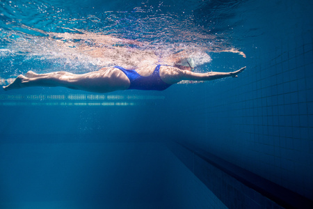 underwater picture of young female swimmer exercising in swimming pool Stock Photo
