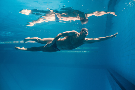 underwater picture of young swimmer in goggles exercising in swimming pool