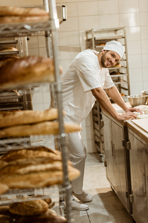 smiling young baker with raw dough at workplace on baking manufacture