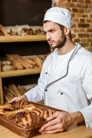 handsome baker holding tray with croissants at pastry store