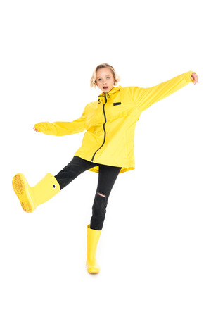 young woman in stylish yellow raincoat and rain boots isolated on white