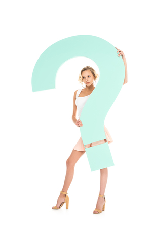 young woman with big question mark in hands looking at camera isolated on white