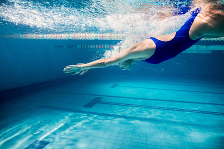 underwater picture of young female swimmer exercising in swimming pool 스톡 콘텐츠