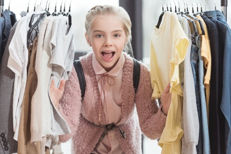 smiling child looking at camera surrounded by clothes on hanger at store Stock Photo