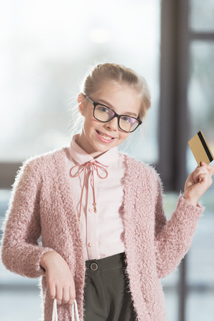 smiling child in glasses holding credit card at shop interior