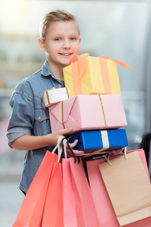 smiling boy holding boxes with paper bags in hands at shop interior Stock Photo