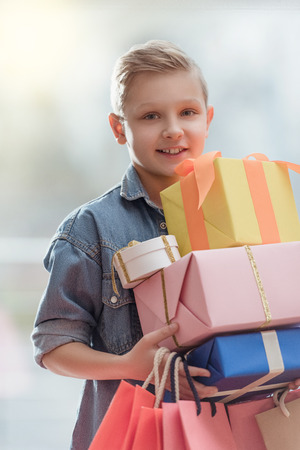 smiling boy holding boxes with colored paper bags in hands at shop interior