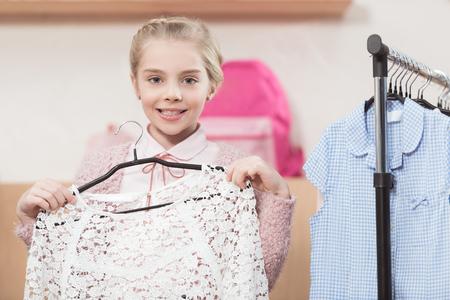 smiling child holding hanger in hands at shop interior