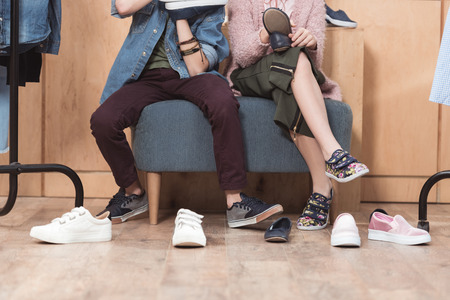 cropped image of kids sitting on sofa surrounded by scattered shoes on floor