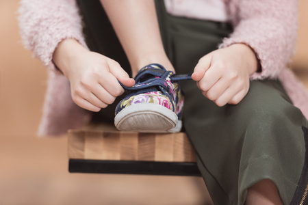 cropped image of child tying lace on sneaker while sitting Banco de Imagens