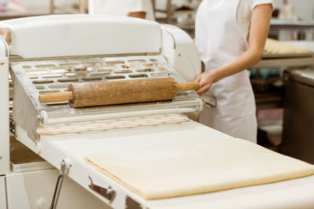cropped shot of female baker with list raw dough on baking manufacture