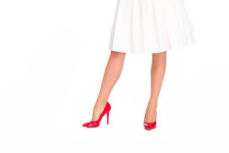 Captura recortada de mujer en tacones rojos y falda aislado en blanco