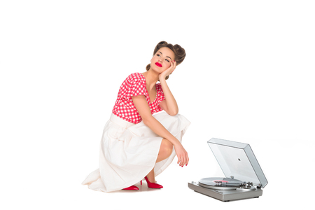 pensive woman in pin up style clothing listening to phonograph isolated on white Stockfoto