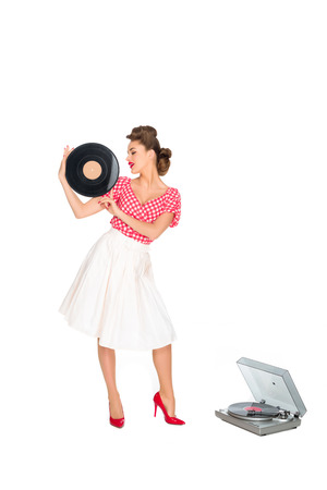 woman in pin up style clothing with vinyl record standing near phonograph isolated on white Stock Photo