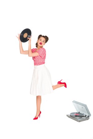 emotional woman in pin up style clothing with vinyl record in hands standing near phonograph isolated on white
